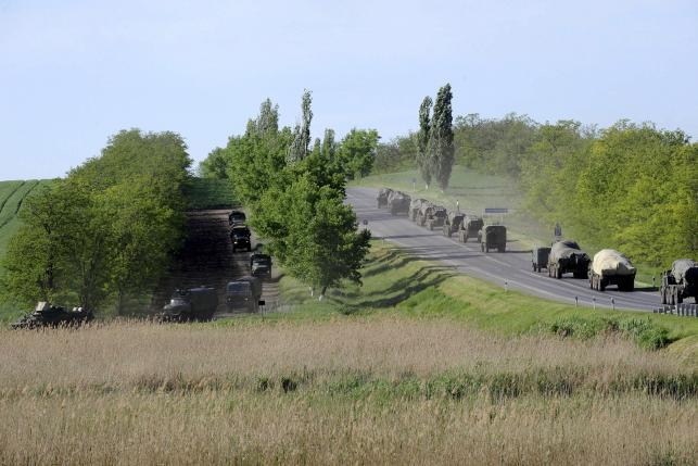 Military vehicles drive along road at Russian southern town of Matveev Kurgan