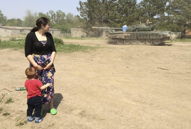 A woman with a boy looks at a tank as it drives through the settlement Khutor Chkalova on its way to the Russian military training ground 'Kuzminsky' near the Russian-Ukrainian border in the Rostov region