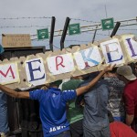 migrants-hold-a-banner-reading-merkel-in-front-of-a-barrier-at-the-border-with-hungary-near-the-village-of-horgos-2